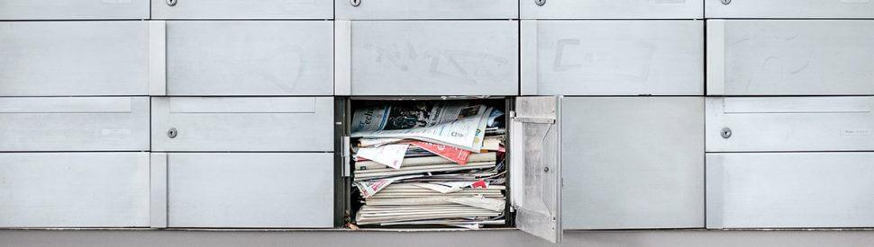 Ein mit Zeitungen vollgestopfter Briefkasten.