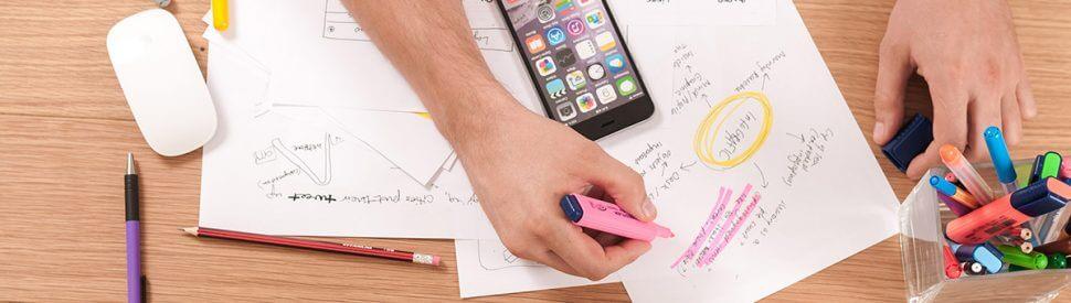 Hände, die mit bunten Stiften auf einem Blatt Papier eine Mindmap malen.